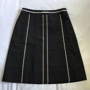 Petite black midi skirt with white embroidery.